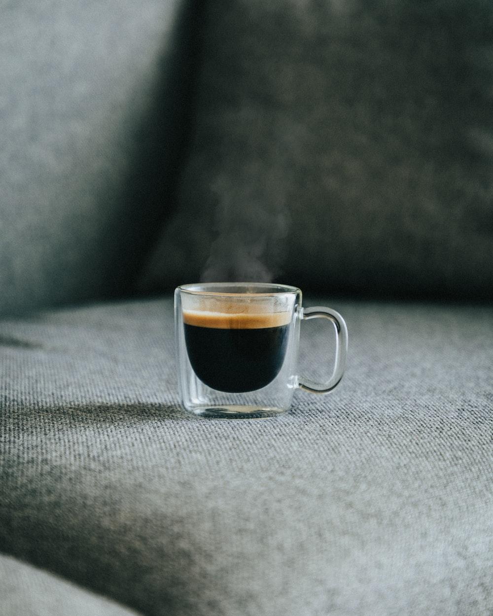 clear glass mug with brown liquid