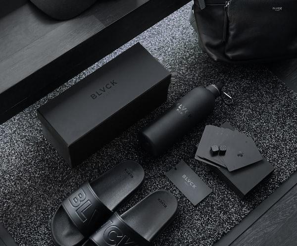 black sony remote control beside black leather bag