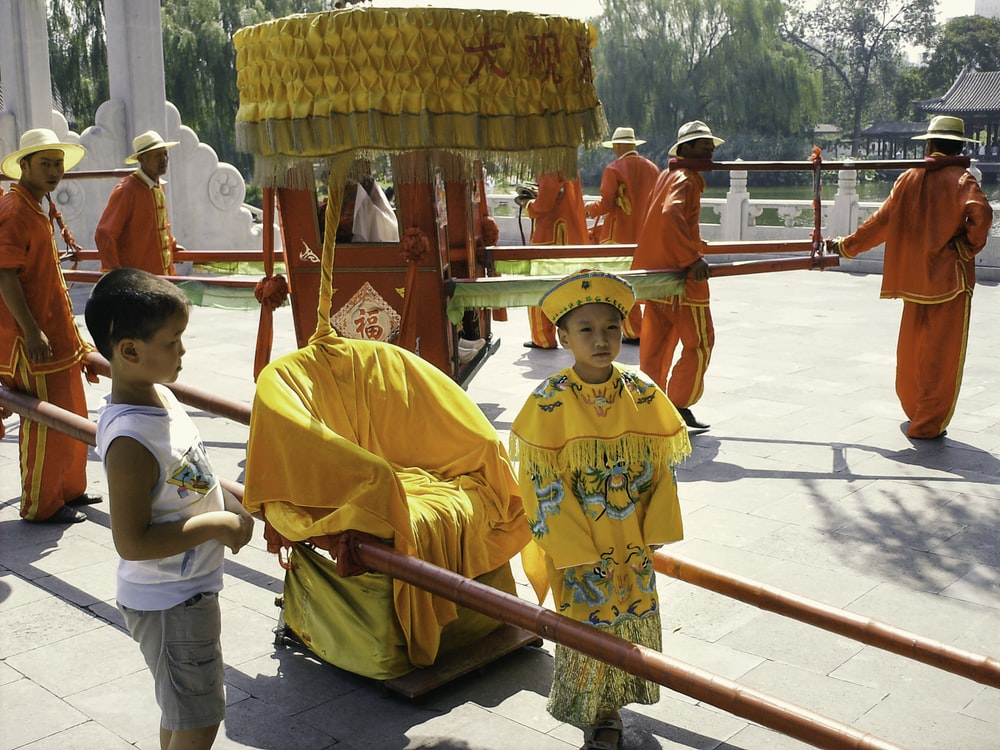 woman in yellow and red traditional dress standing beside red metal railings