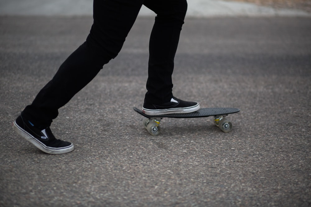 person in black pants and black shoes standing on skateboard during daytime