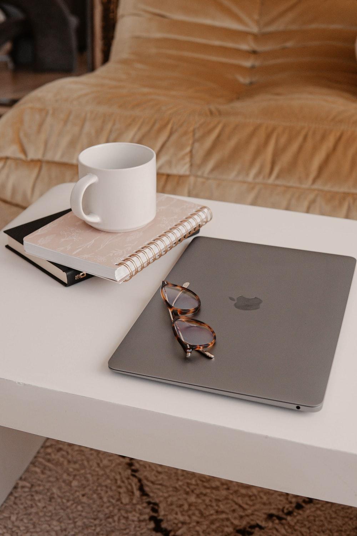 silver macbook beside white ceramic mug on white table