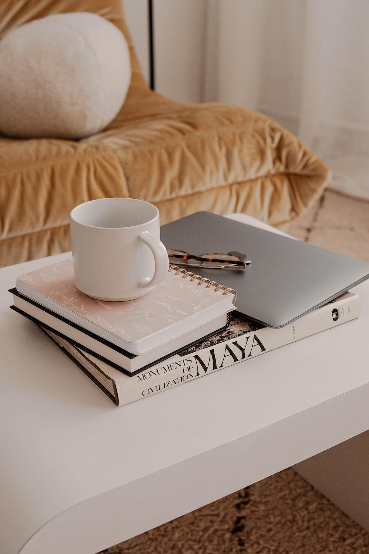 white ceramic mug on white book