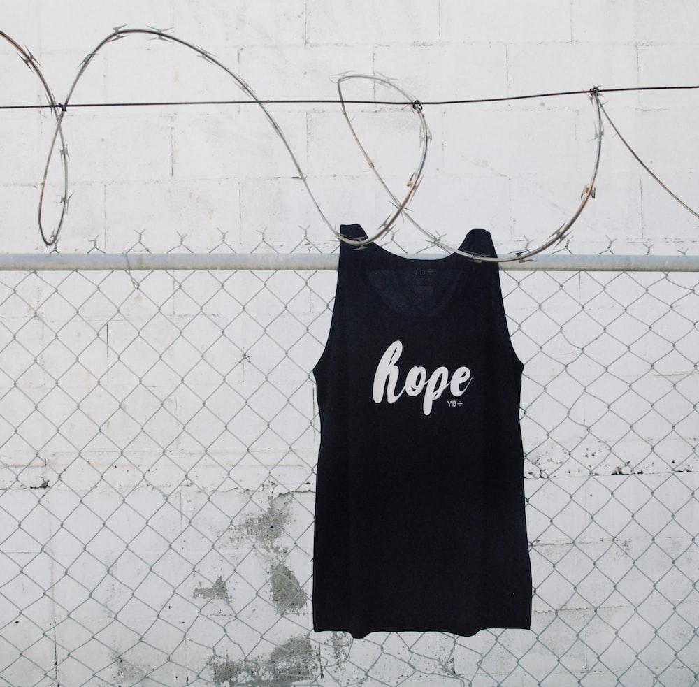 black and white adidas shirt hanging on gray metal fence