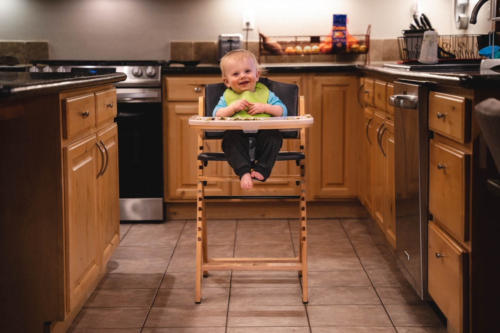 baby in green shirt sitting on brown wooden high chair
