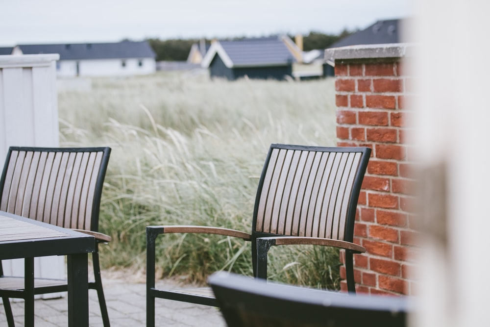 black wooden armchair beside brown brick wall