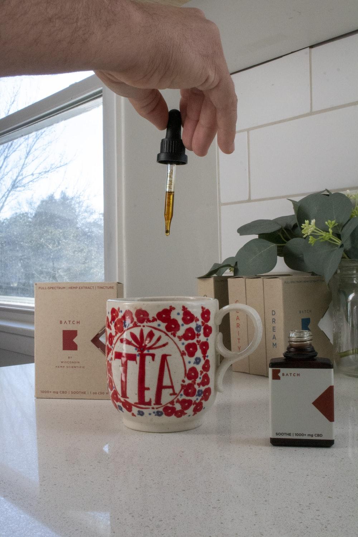 white and red ceramic mug