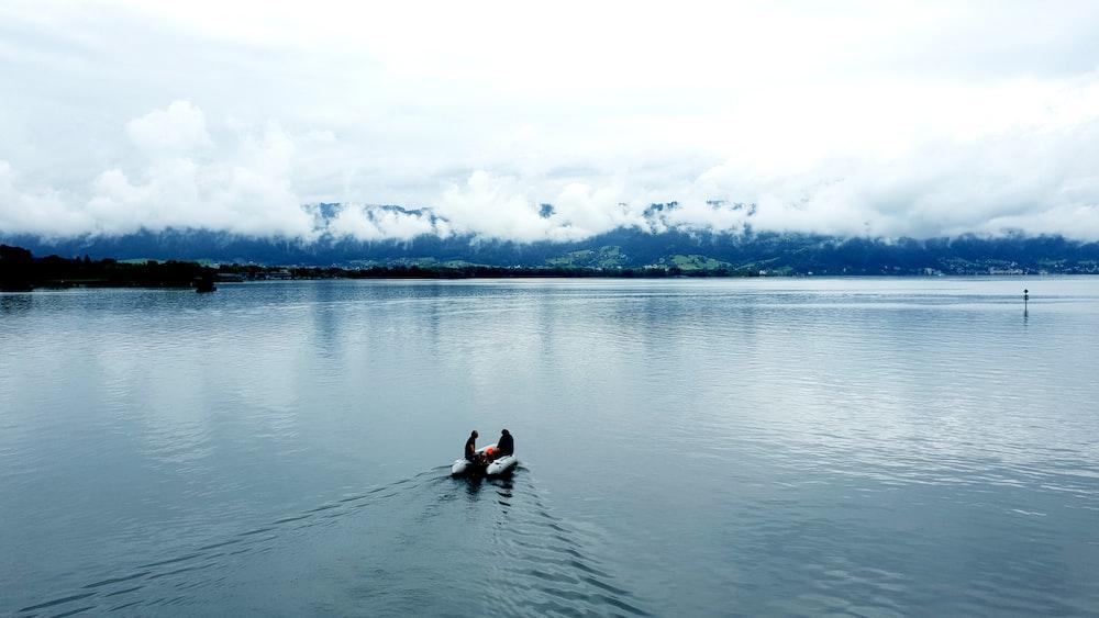 man in black wet suit riding on black kayak on body of water during daytime