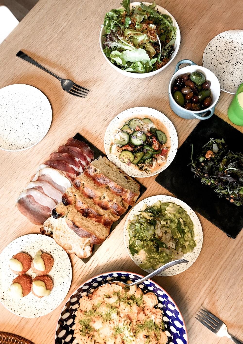 sliced meat on white ceramic plate beside green vegetable salad on white ceramic bowl