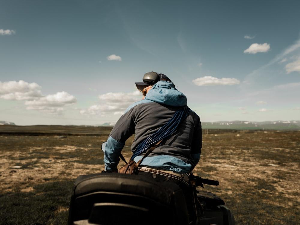 man in blue jacket and black pants sitting on black motorcycle