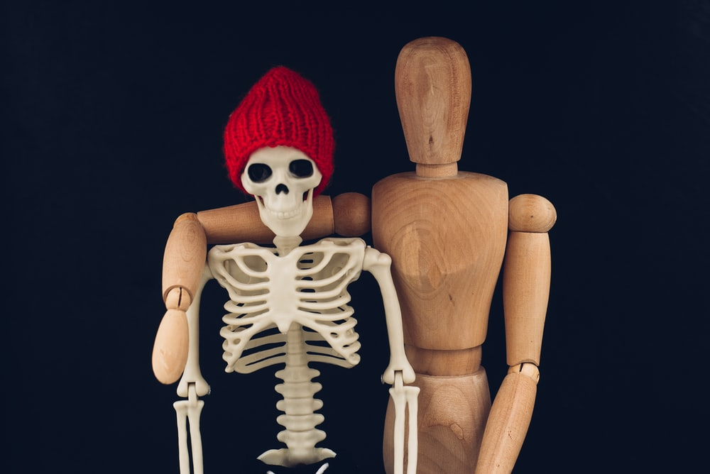 skeleton with red knit cap and white gloves