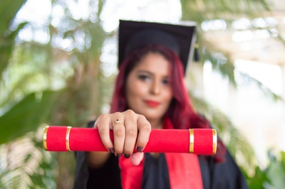 woman in red long sleeve shirt holding red and black academic hat diploma teams background