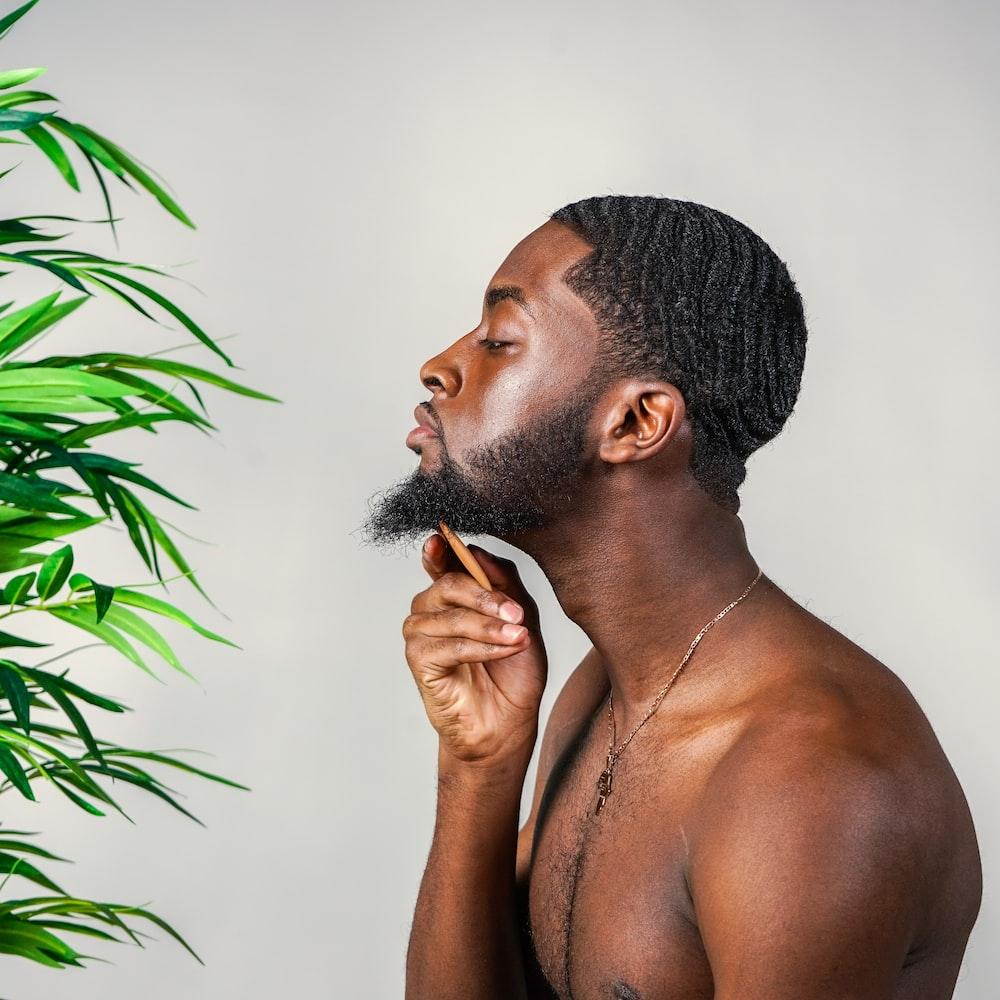 topless man standing near green plant