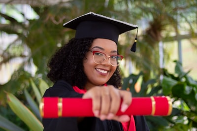 smiling woman wearing academic dress and black academic hat diploma teams background