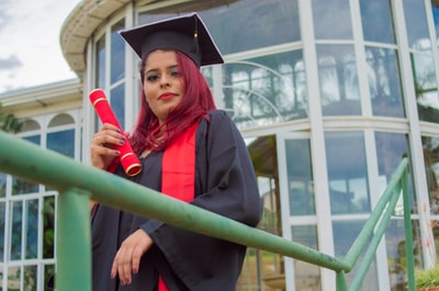 woman in academic gown holding red rose diploma teams background