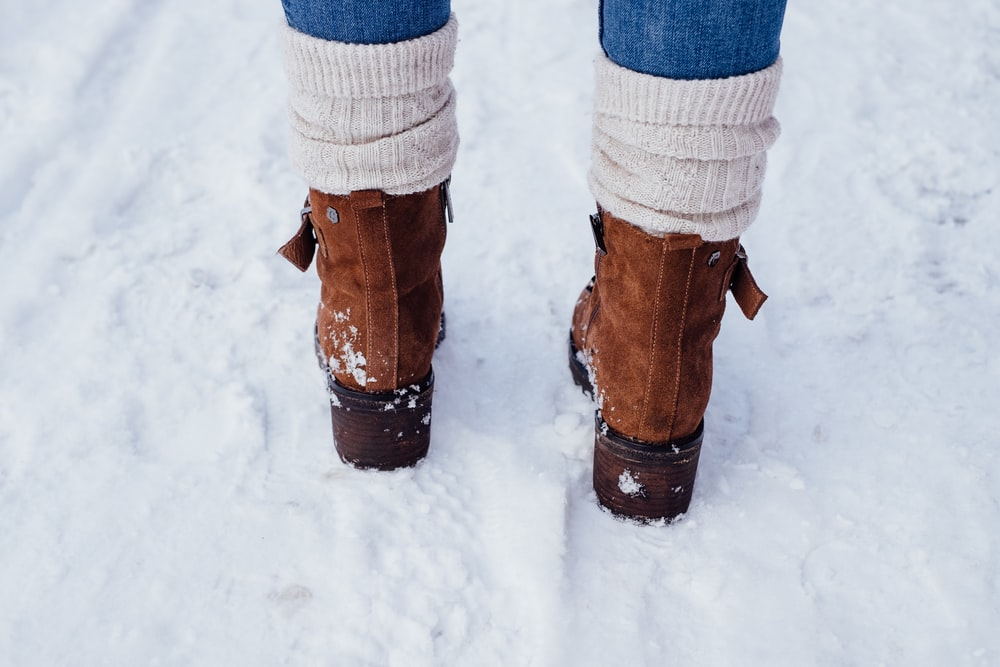 person in brown leather boots standing on snow covered ground