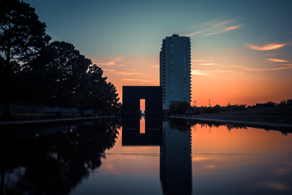 body of water near trees and high rise building during sunset