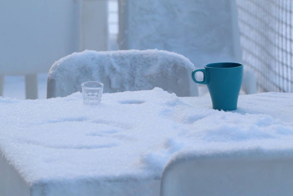 blue ceramic mug on snow covered ground