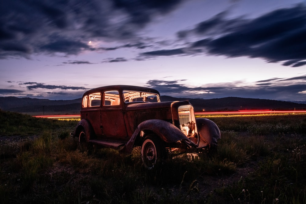 brown vintage car on green grass field under cloudy sky during daytime