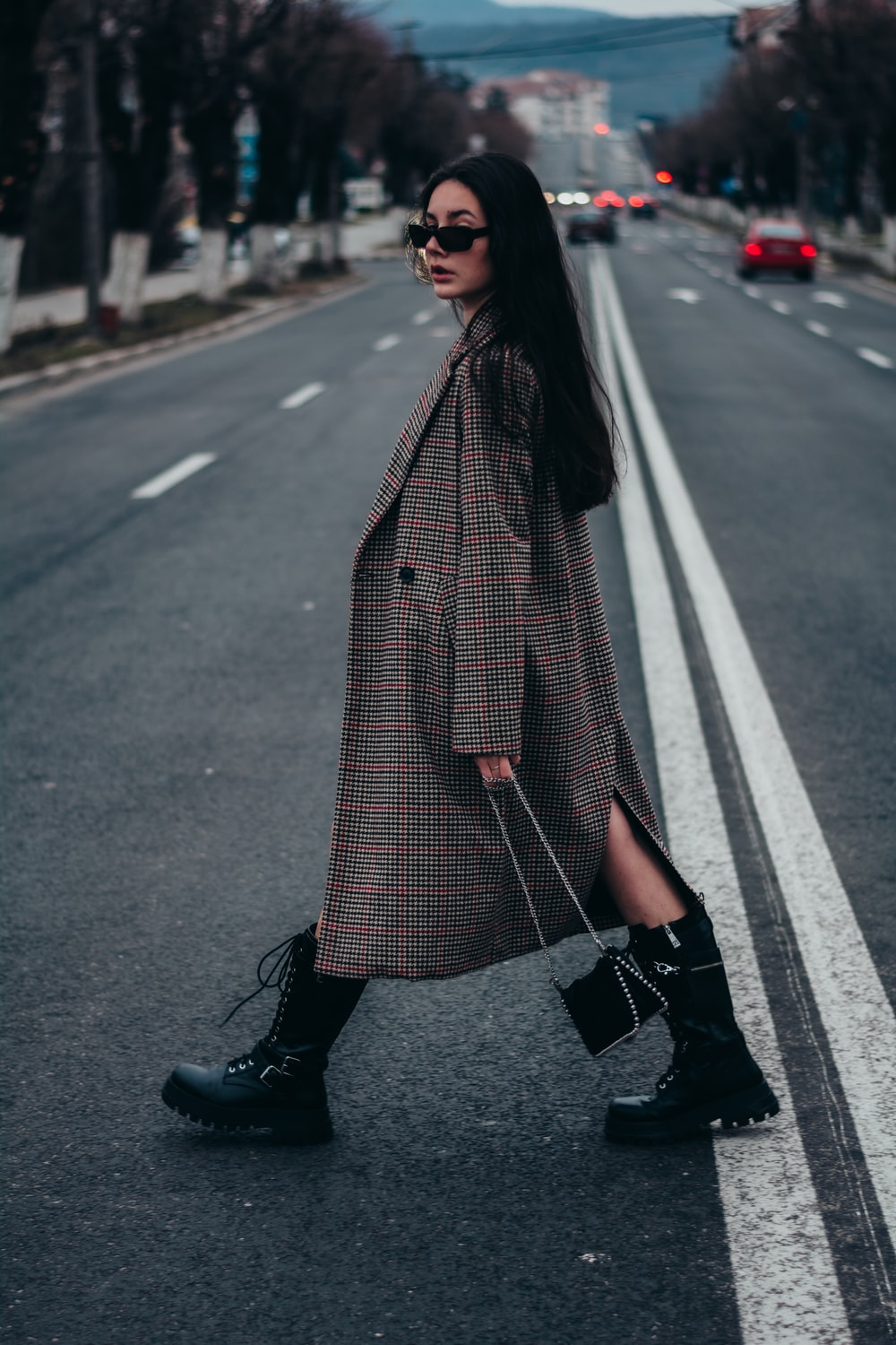 woman in black coat standing on the road