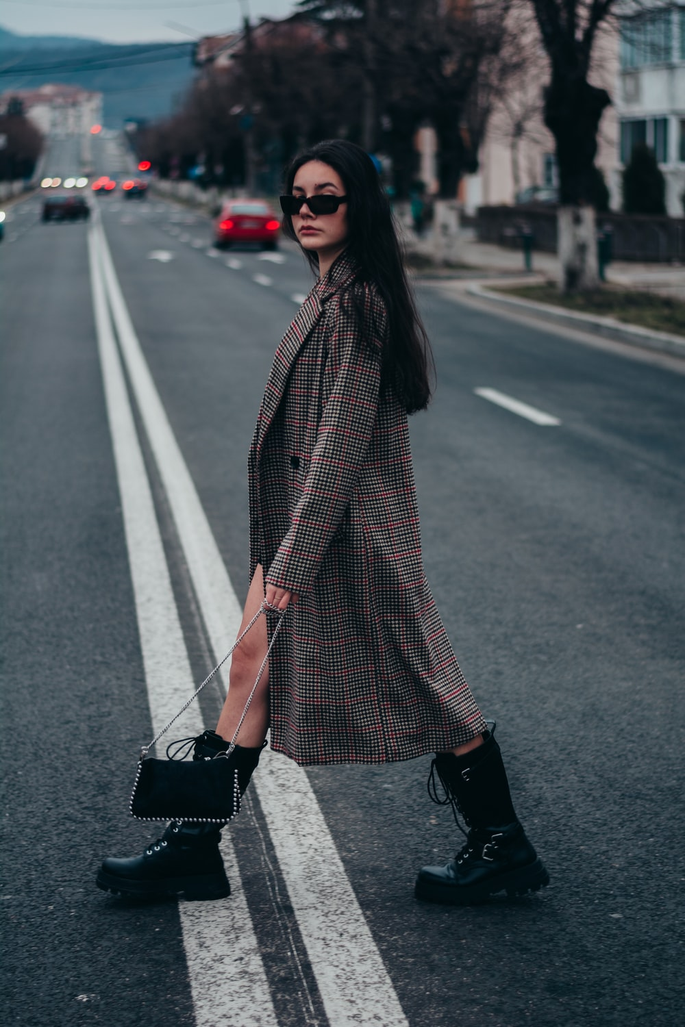 woman in black and white scarf standing on the road