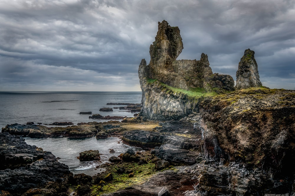 rock formation on sea under cloudy sky during daytime