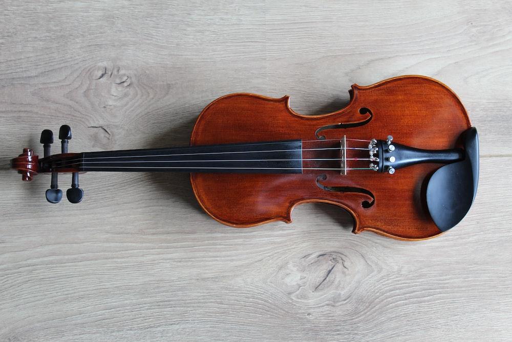 brown violin on white textile