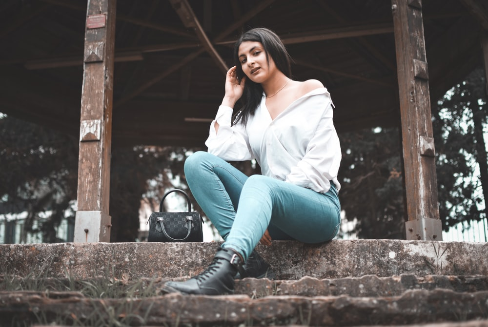 woman in white long sleeve shirt and blue denim jeans sitting on brown concrete stairs