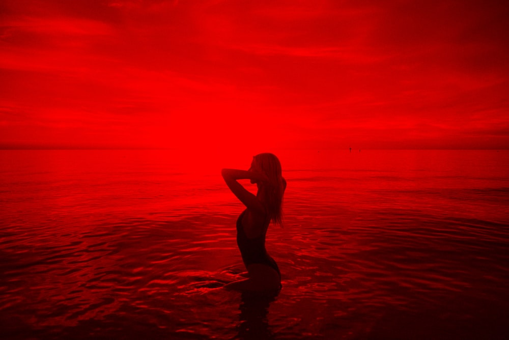 woman in black bikini walking on beach during sunset