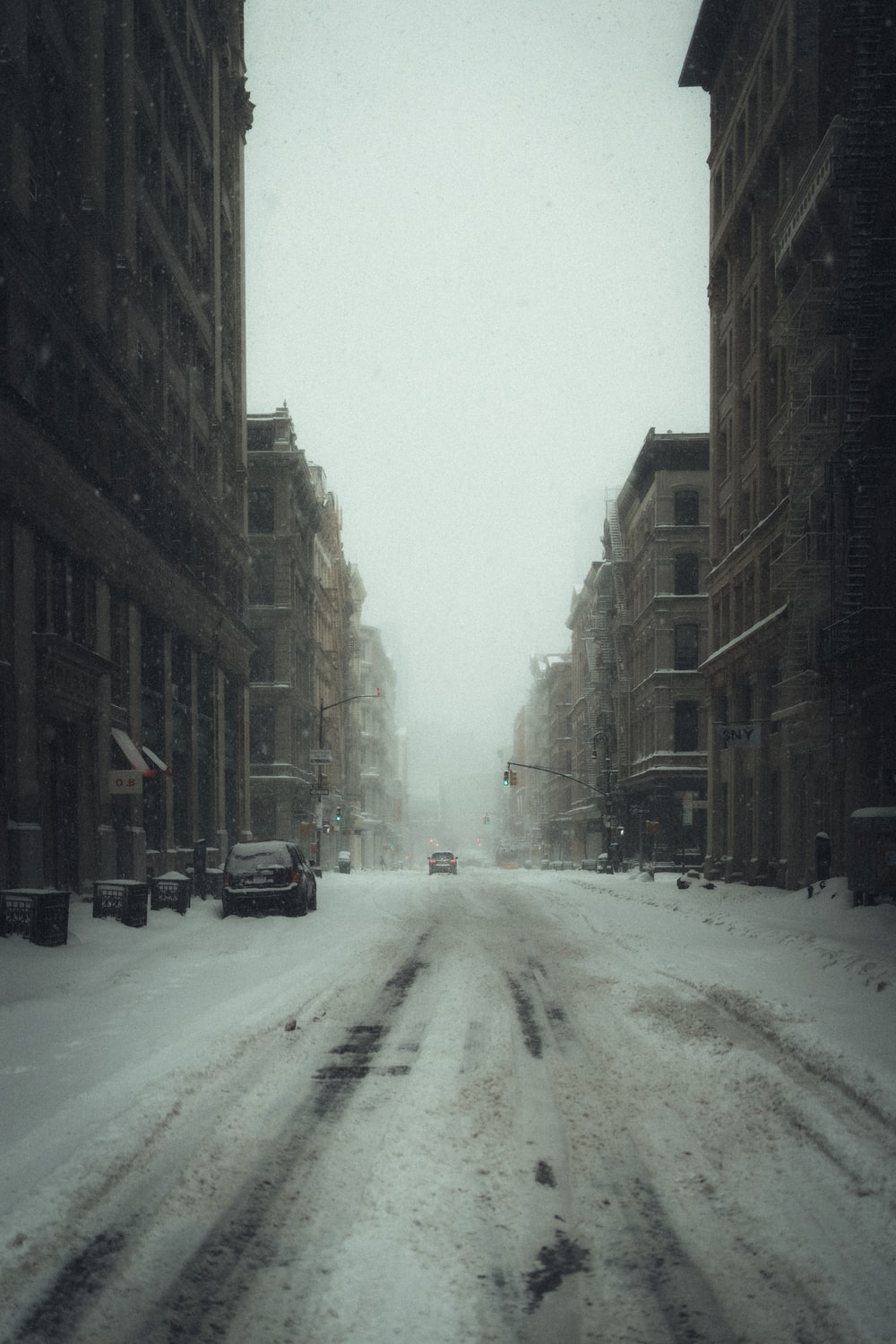snow covered road between buildings during daytime