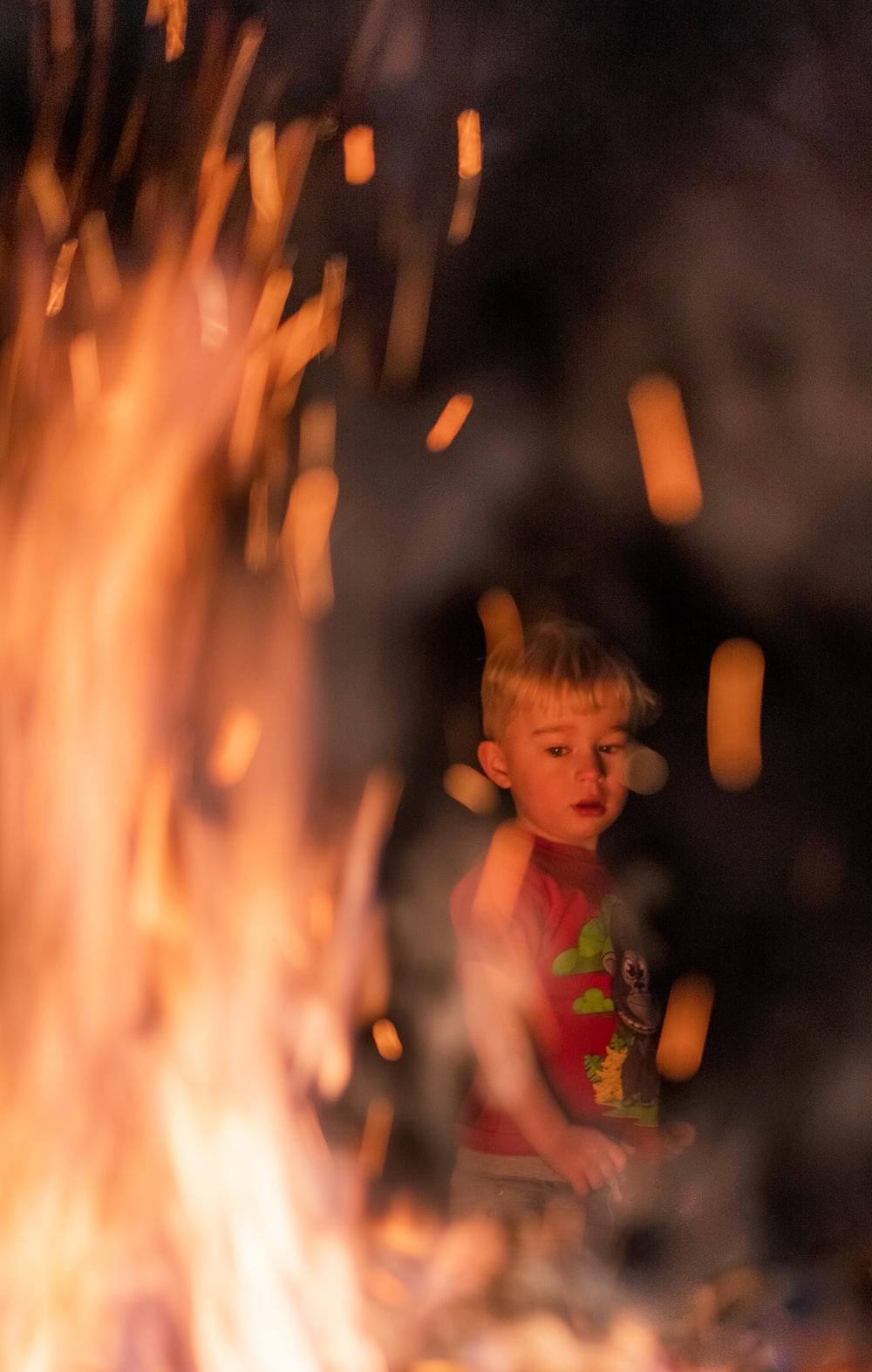 boy in green and white floral shirt standing near fire