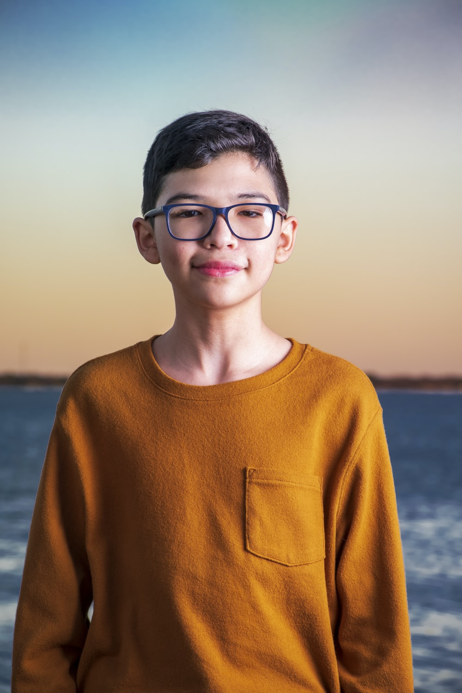 boy in brown crew neck sweater wearing black framed eyeglasses