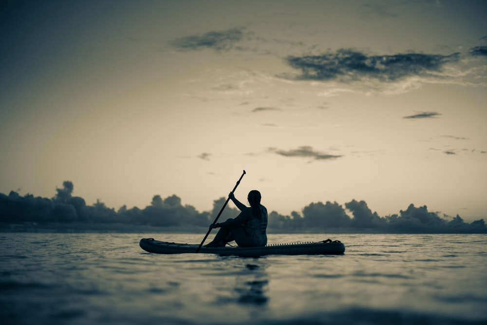 silhouette of man riding on kayak on body of water during daytime