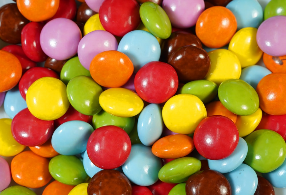 assorted color candies on brown wooden table