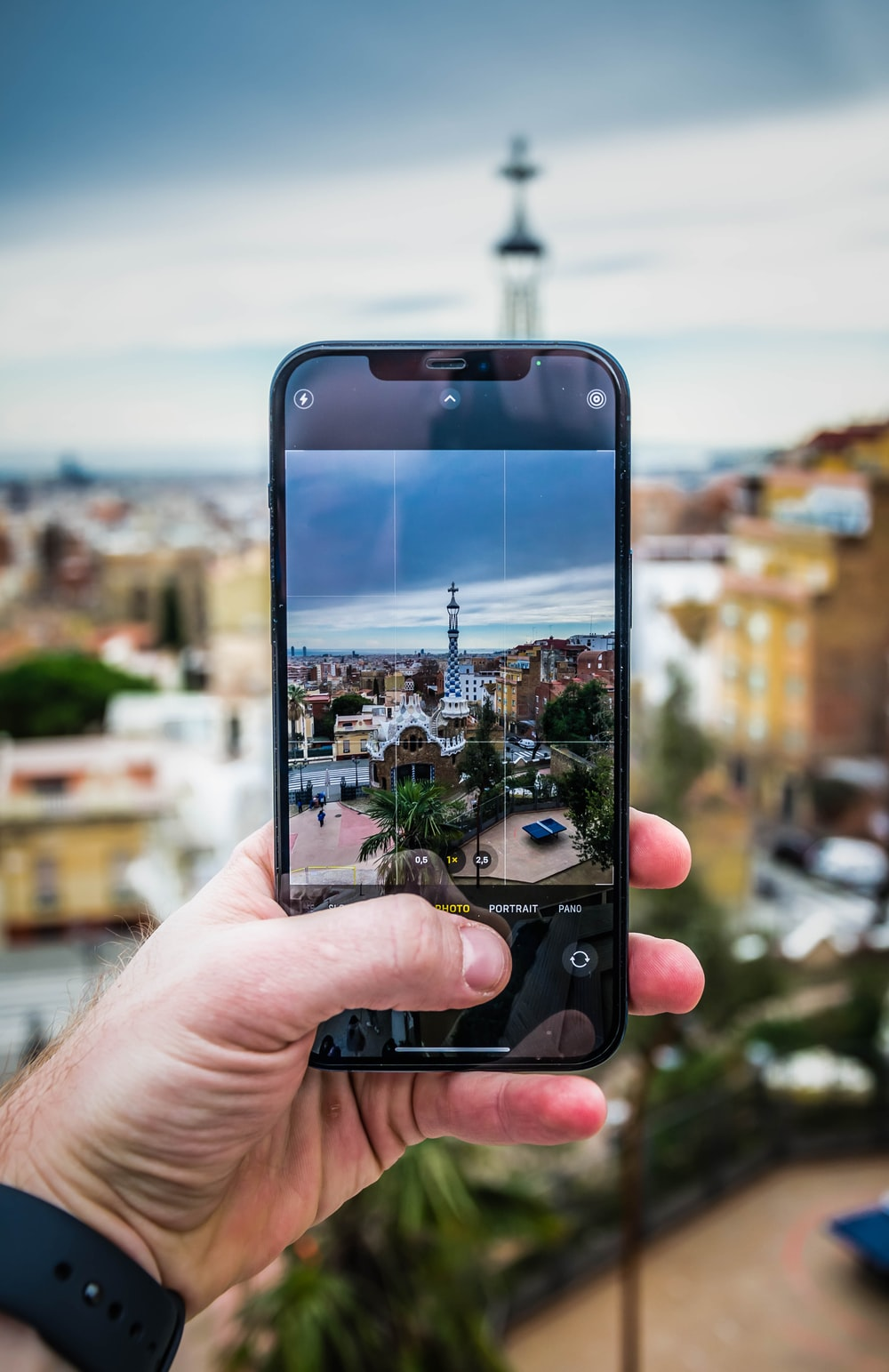 person holding iphone taking photo of city buildings during daytime