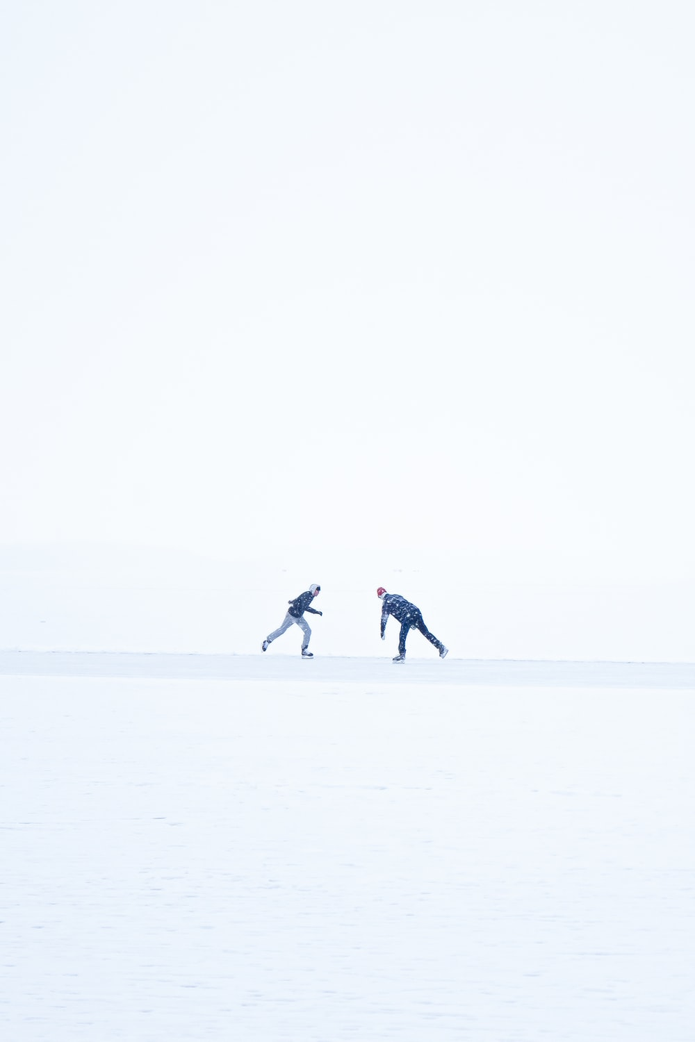 2 person walking on snow covered field during daytime