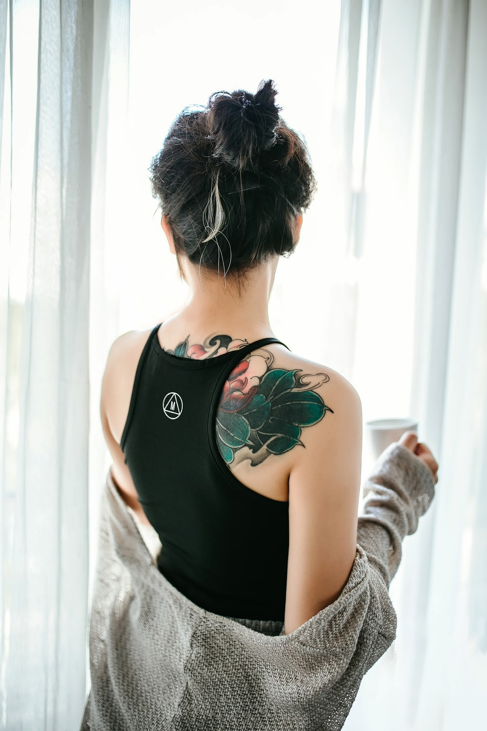 woman in black tank top with green floral tattoo on her back
