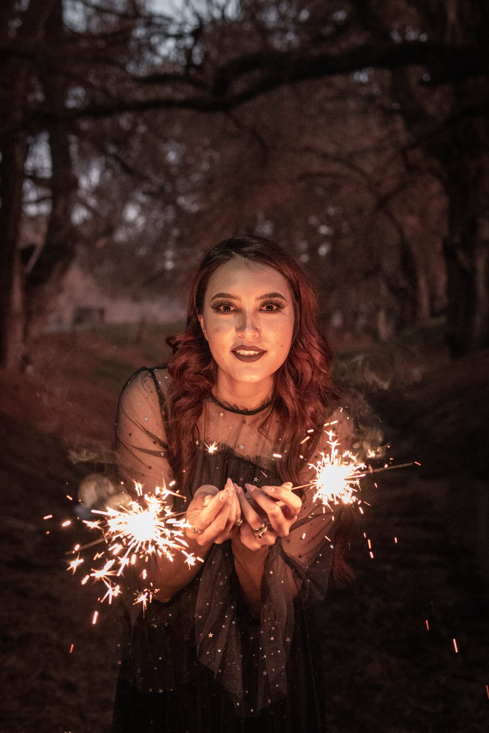 woman in brown long sleeve shirt holding sparkler