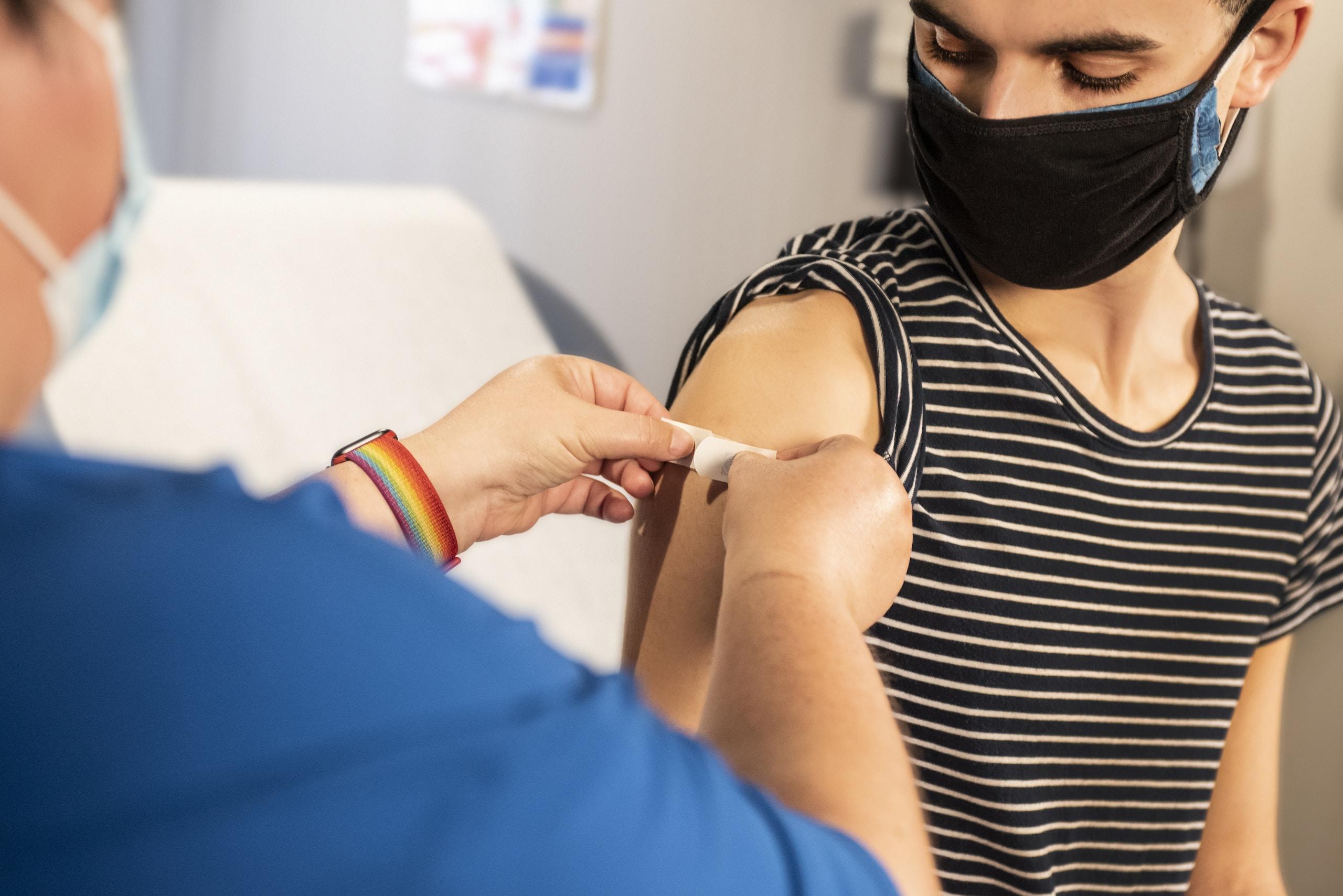 Messenger-RNA-Impfstoffe, Person in blauem Langarmhemd mit weißem Textil