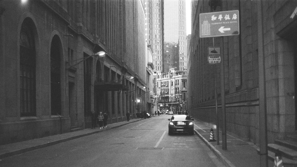 grayscale photo of cars on road between buildings