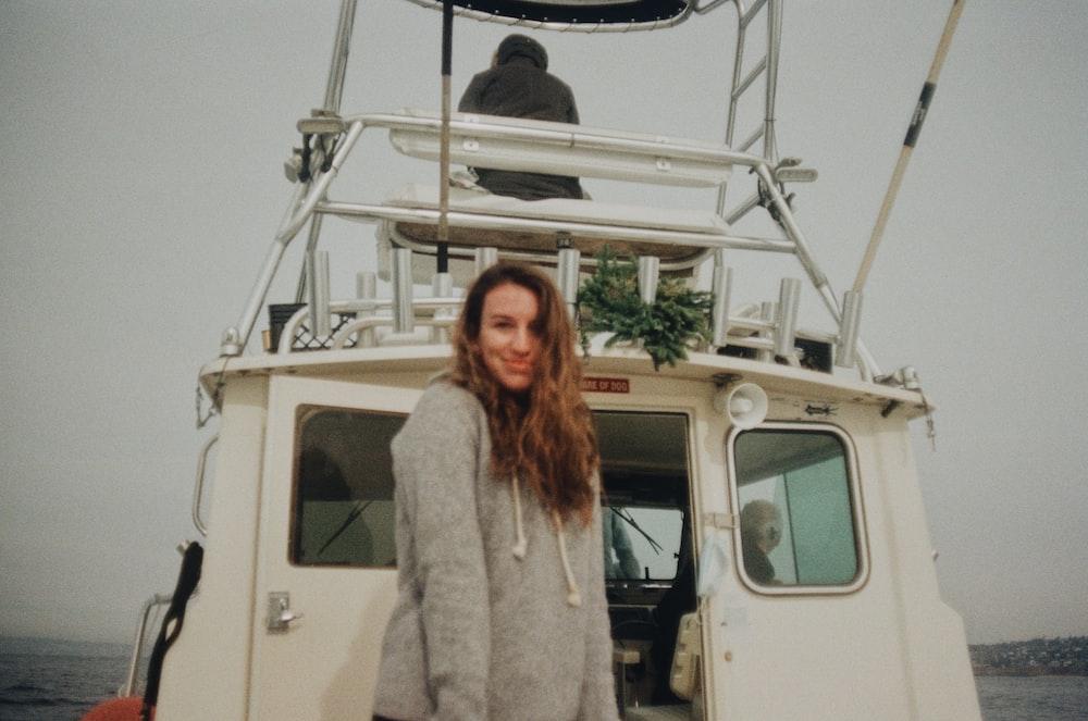 woman in white fur coat standing beside white van