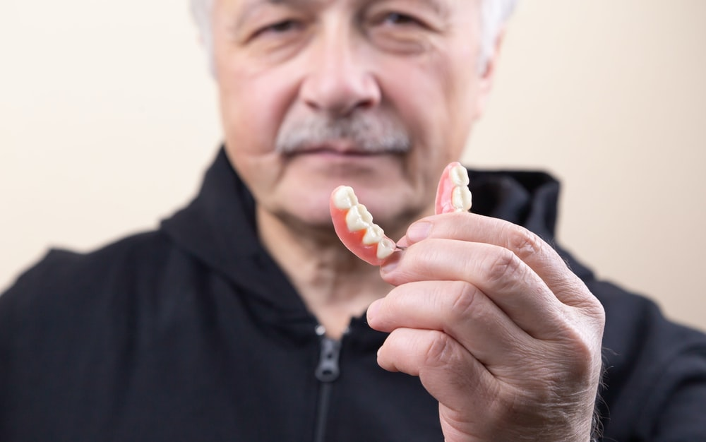 man in black shirt holding white candy