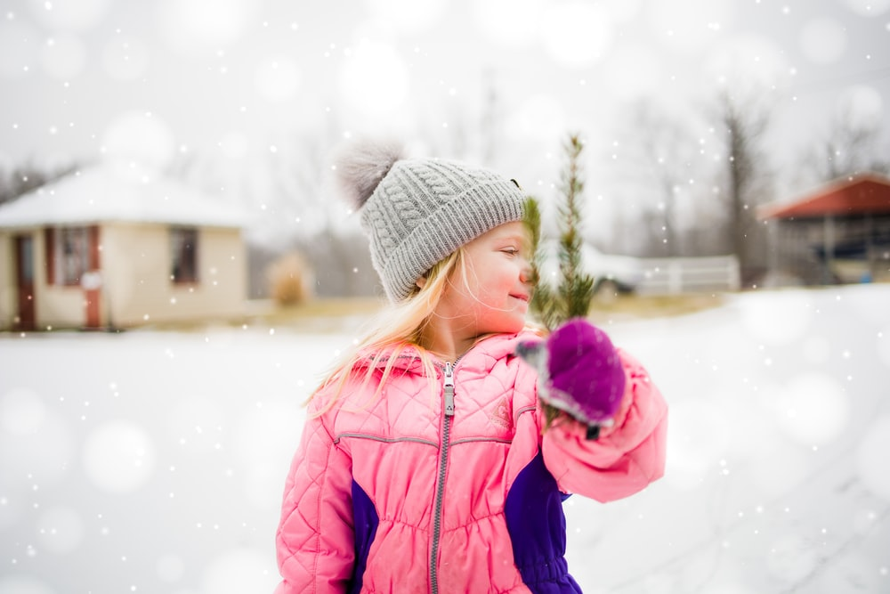 girl in blue bubble jacket and gray knit cap standing on snow covered ground during daytime
