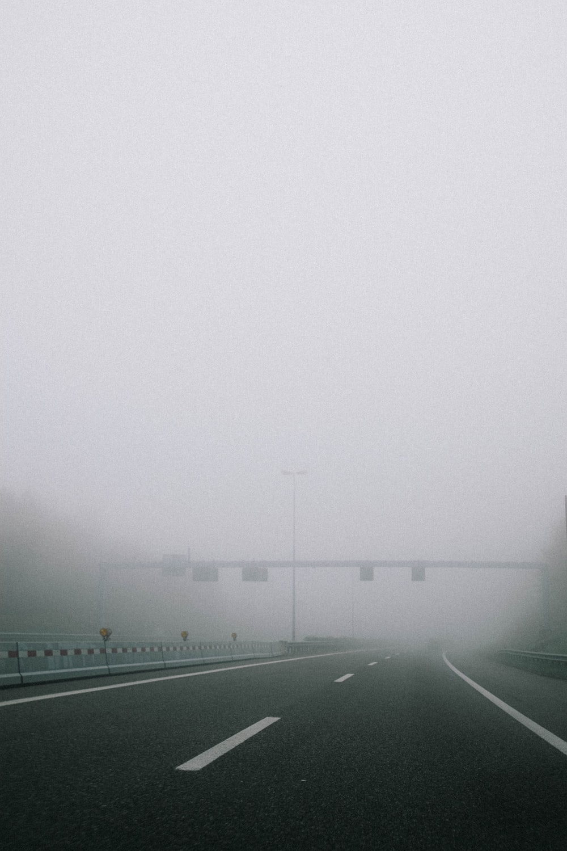 gray asphalt road during foggy weather