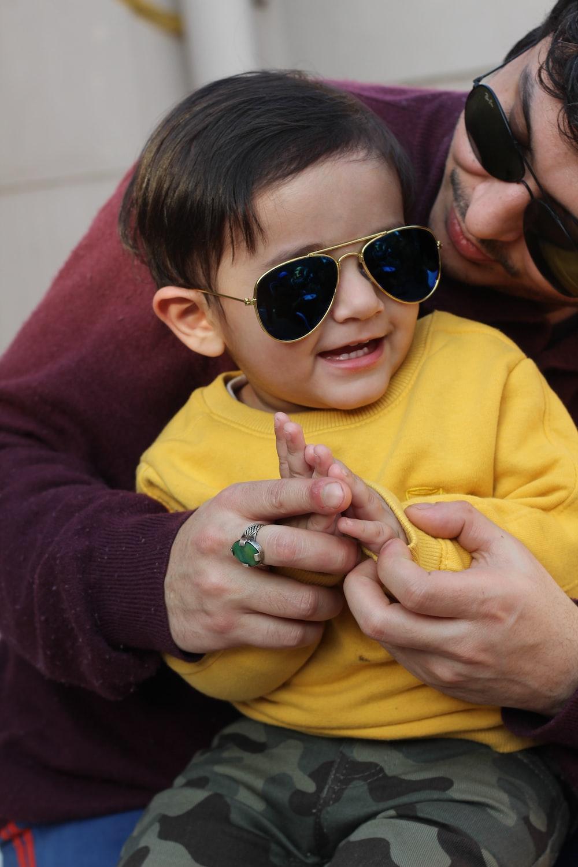 boy in yellow hoodie wearing black sunglasses