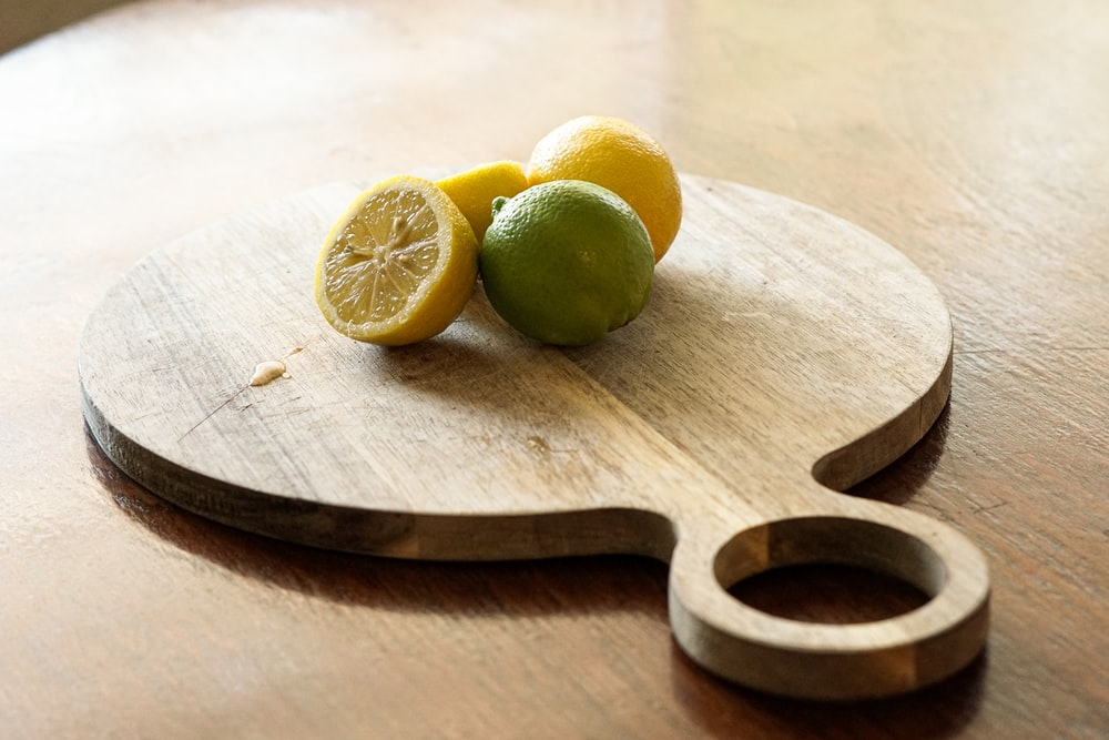 sliced lemon on brown wooden chopping board