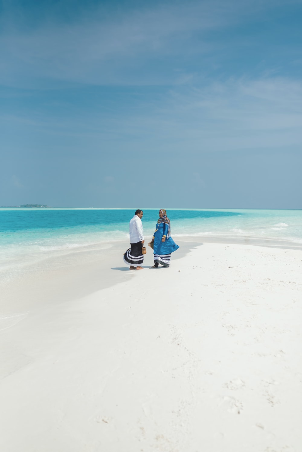 couple sitting on white sand beach during daytime