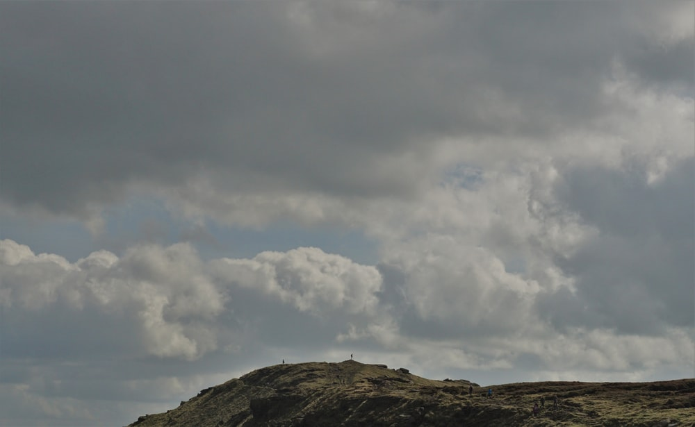 white clouds over brown mountain