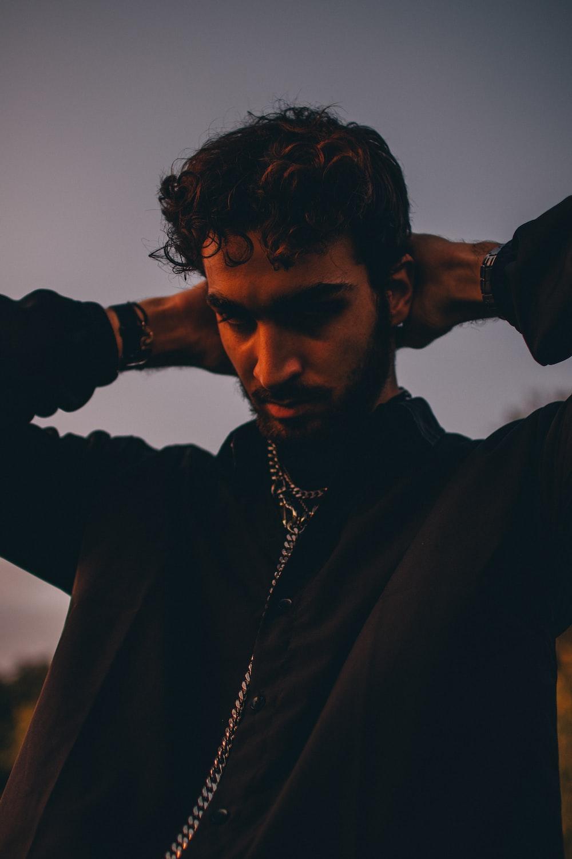 man in black coat wearing silver necklace