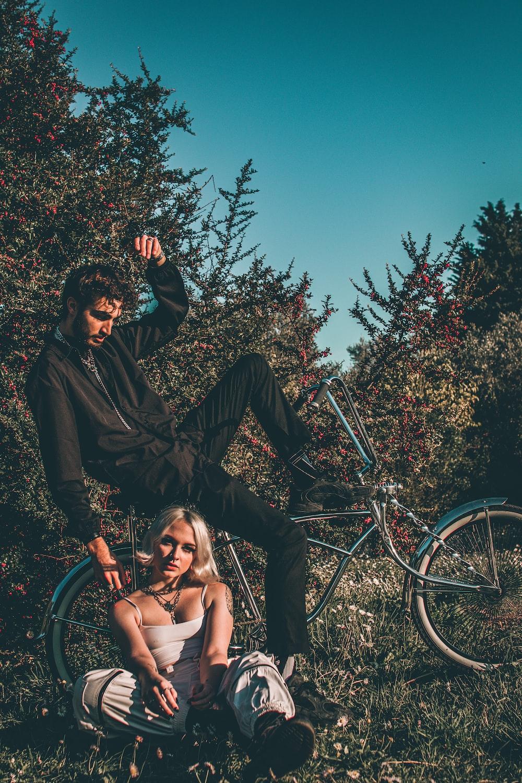 man and woman sitting on black metal frame near green bicycle during daytime