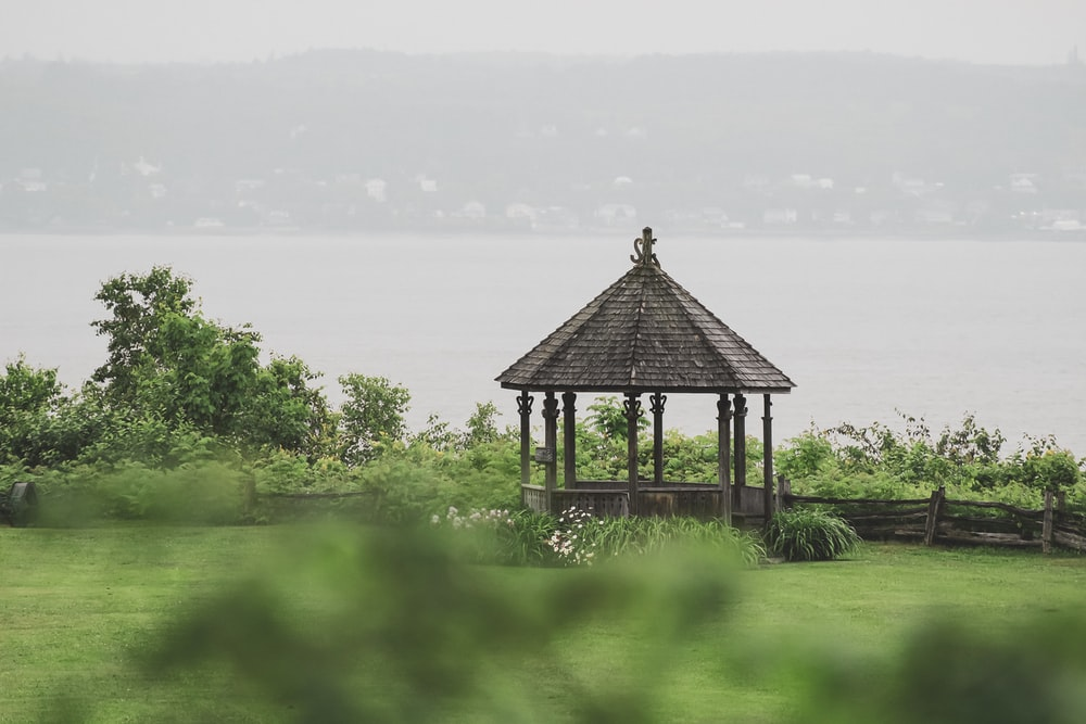 black wooden gazebo on green grass field near body of water during daytime